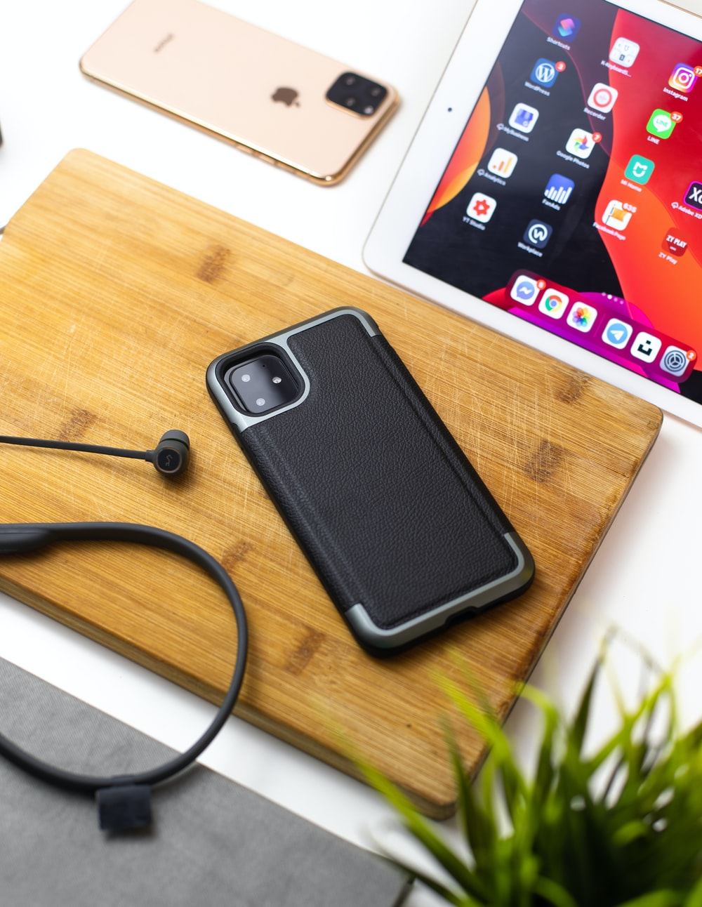 iPhone 11 on wood chopping board beside iPad and rose gold iPhone 11