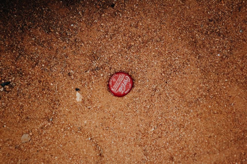 red Coca-Cola bottle cap on ground