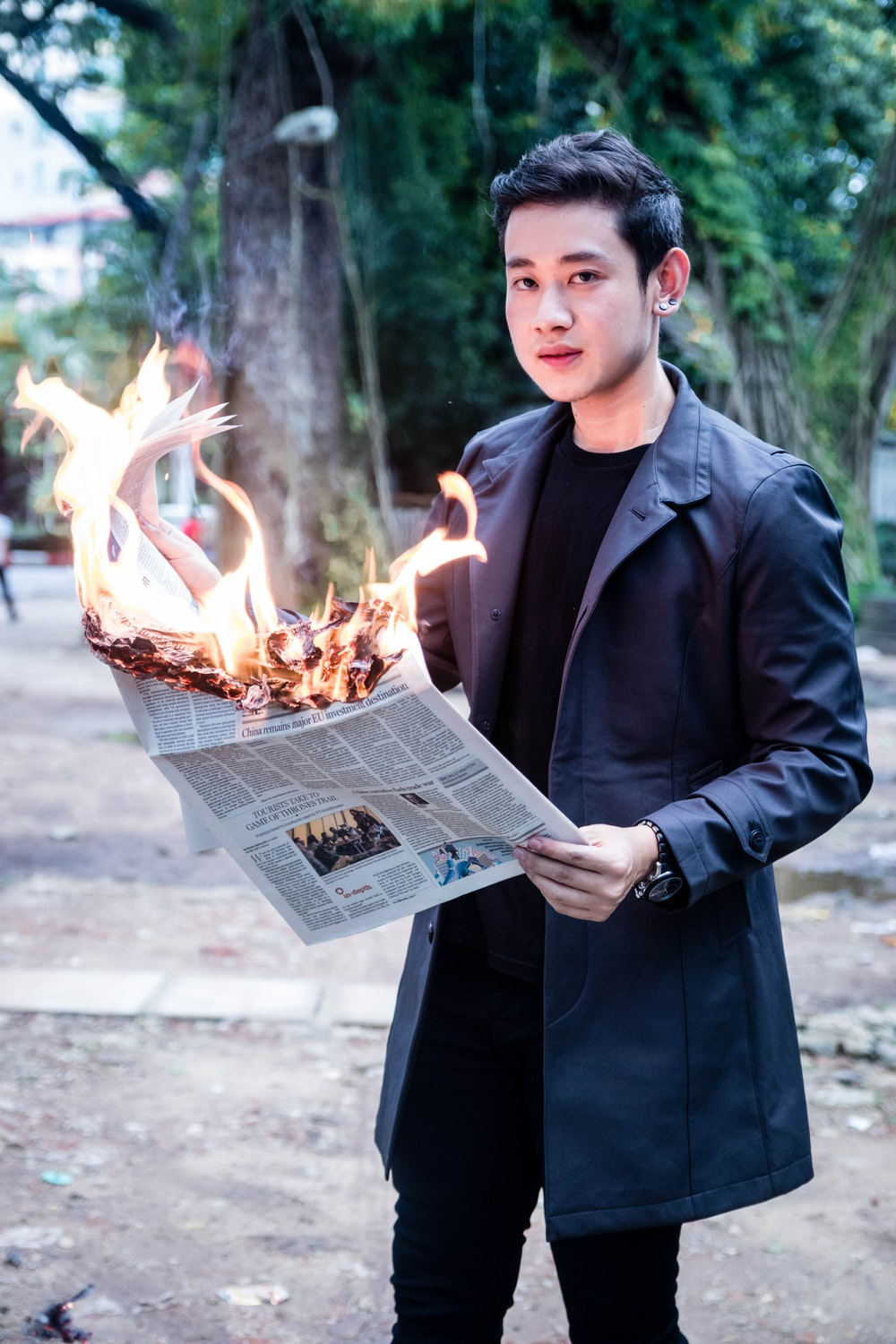 man holding newspaper in fire