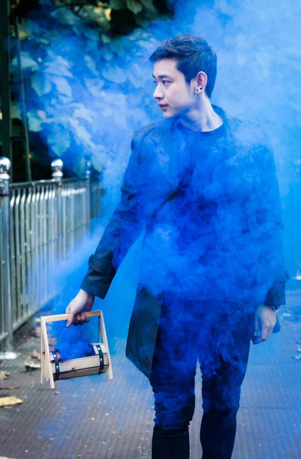 man wearing black jacket holding wooden box with blue smoke coming out
