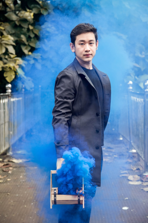 man in gray coat holding machine emitting blue smoke