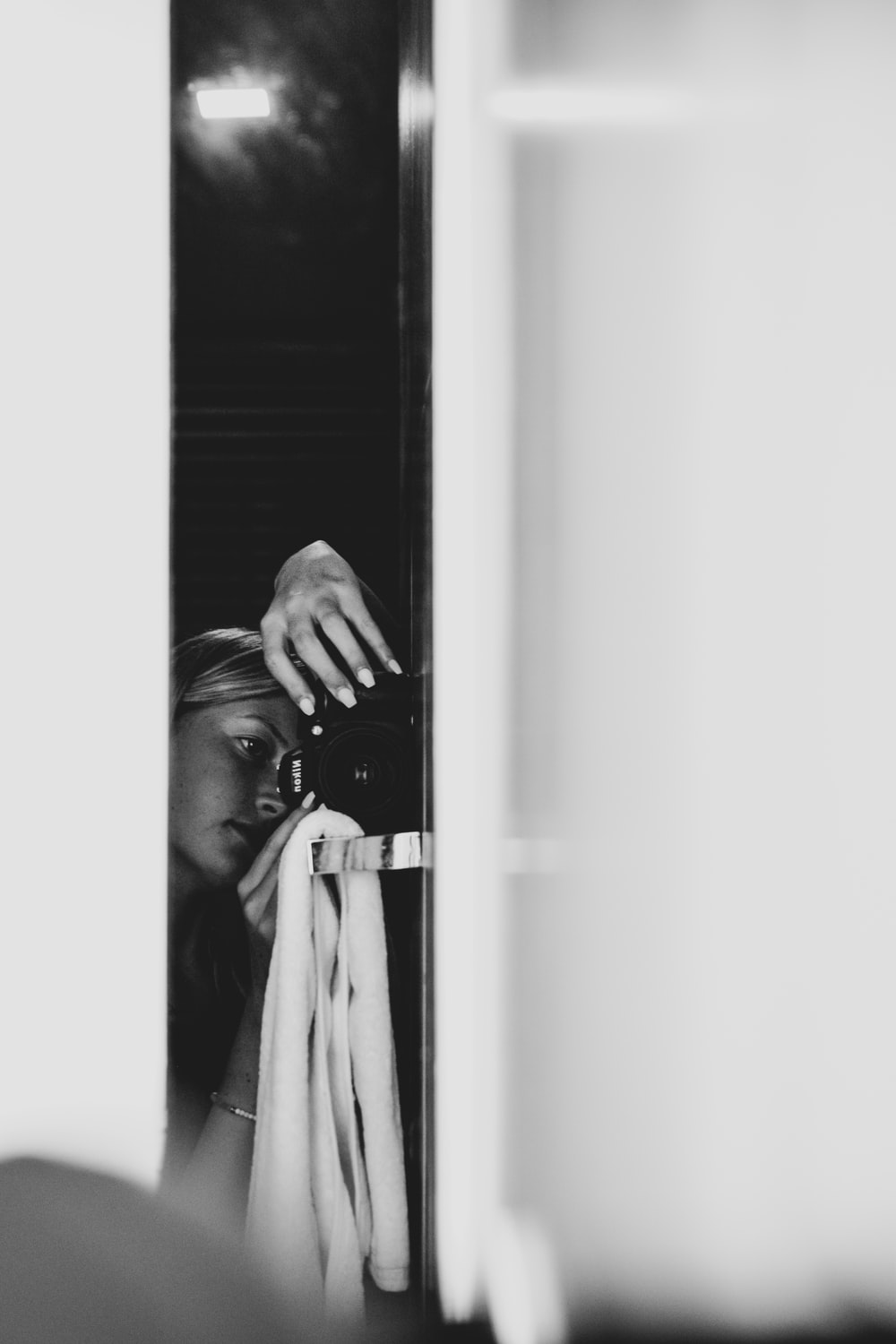 grayscale photography of woman leaning on glass