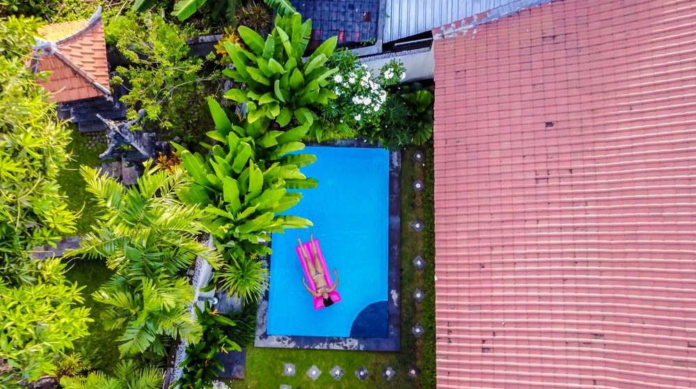 aerial photography of a person lying on a floater in the swimming pool