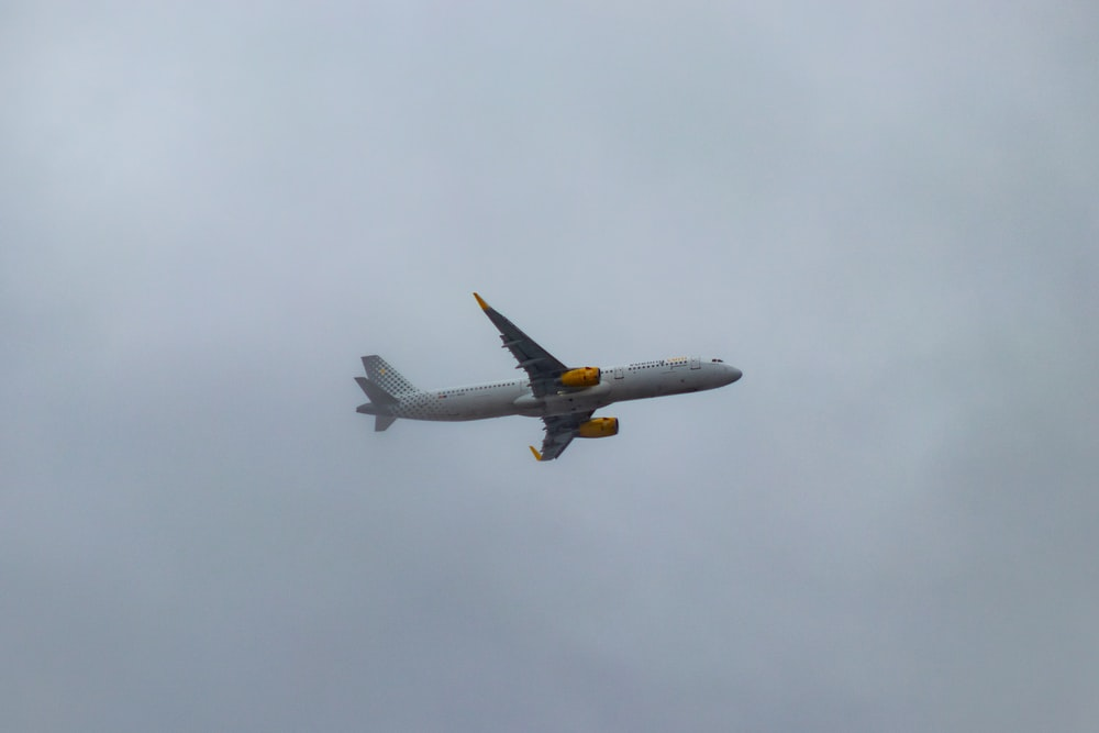 white and orange airliner flying on cloudy sky