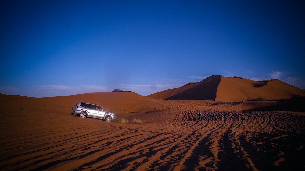 silver SUV on brown desert during daytime