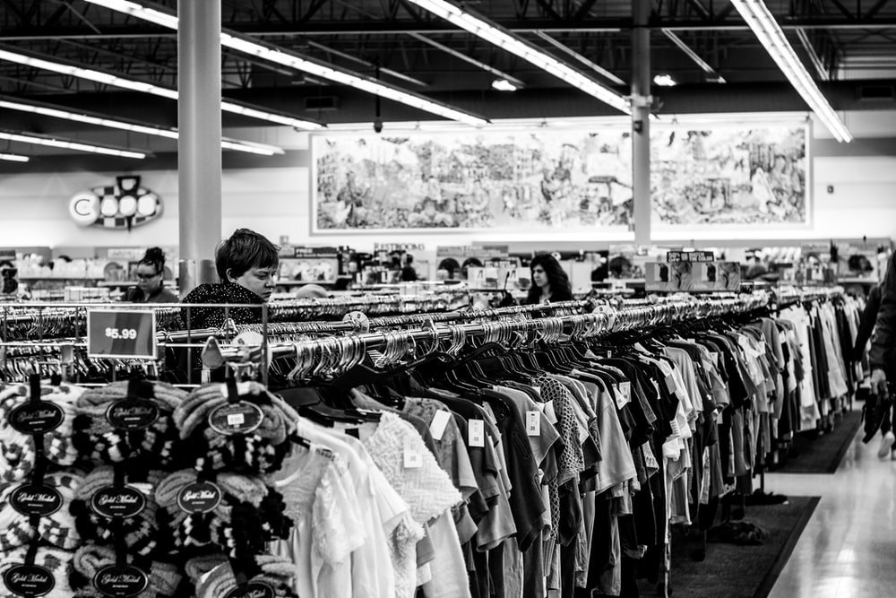 grayscale photography of people inside a clothing shop