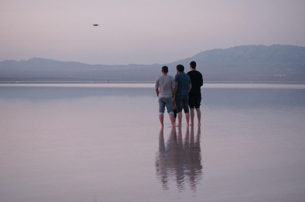 three men standing on shore