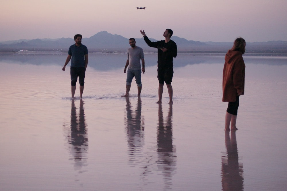 four people standing on wet ground