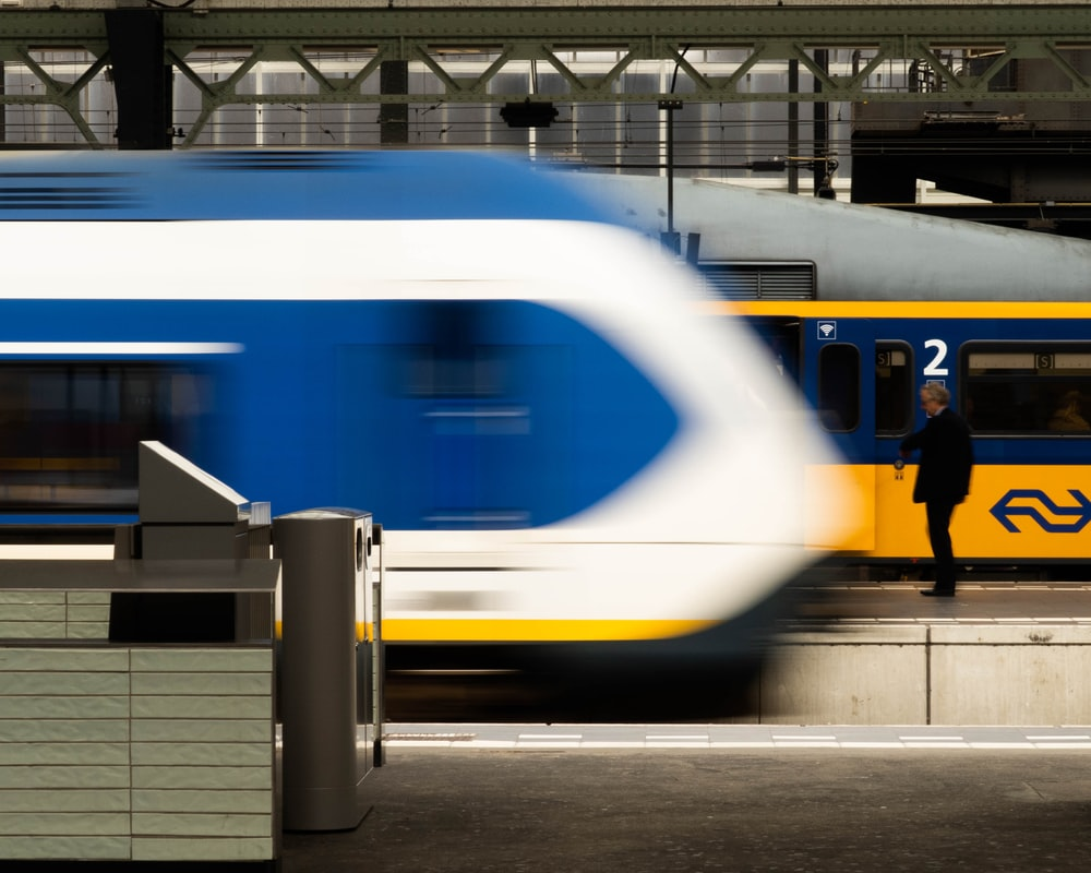 person standing near yellow and blue train