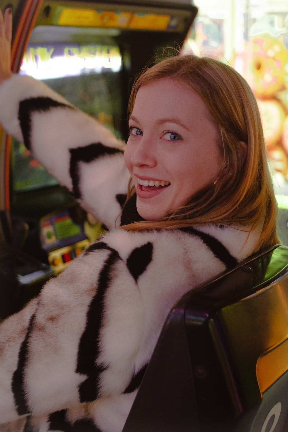 selective focus photography of smiling woman wearing white and black striped fur coat