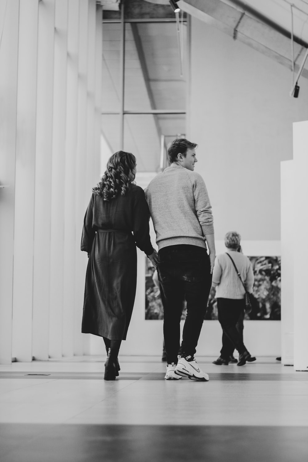 grayscale photography of man and woman walking inside building