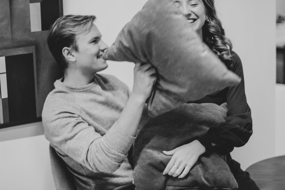 grayscale photography of man and woman pillow fighting