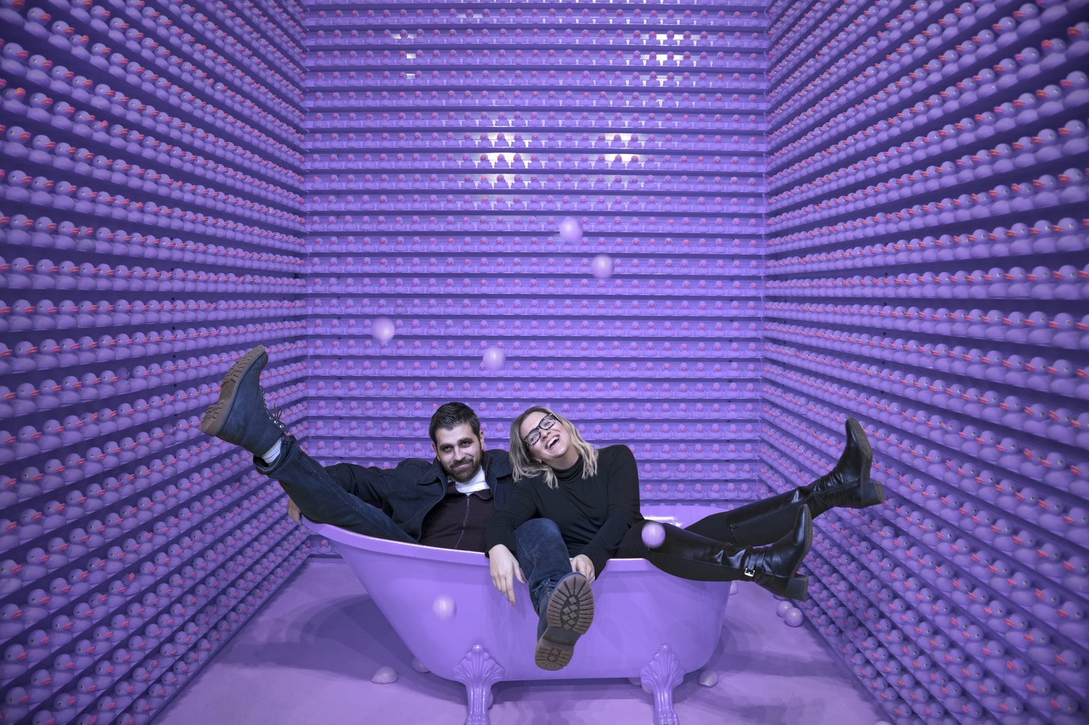 man and woman sitting in a purple bathtub
