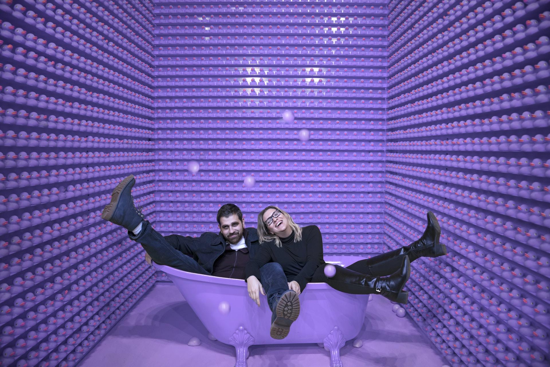 man and woman sitting in a purple bathtub