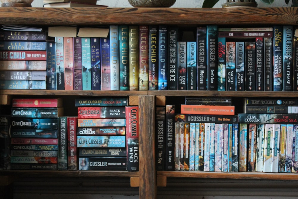 books stacked on a wooden shelving