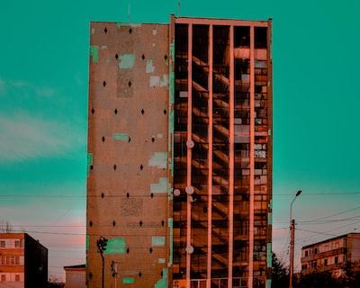 brown concrete high-rise building under a blue calm sky tudor teams background