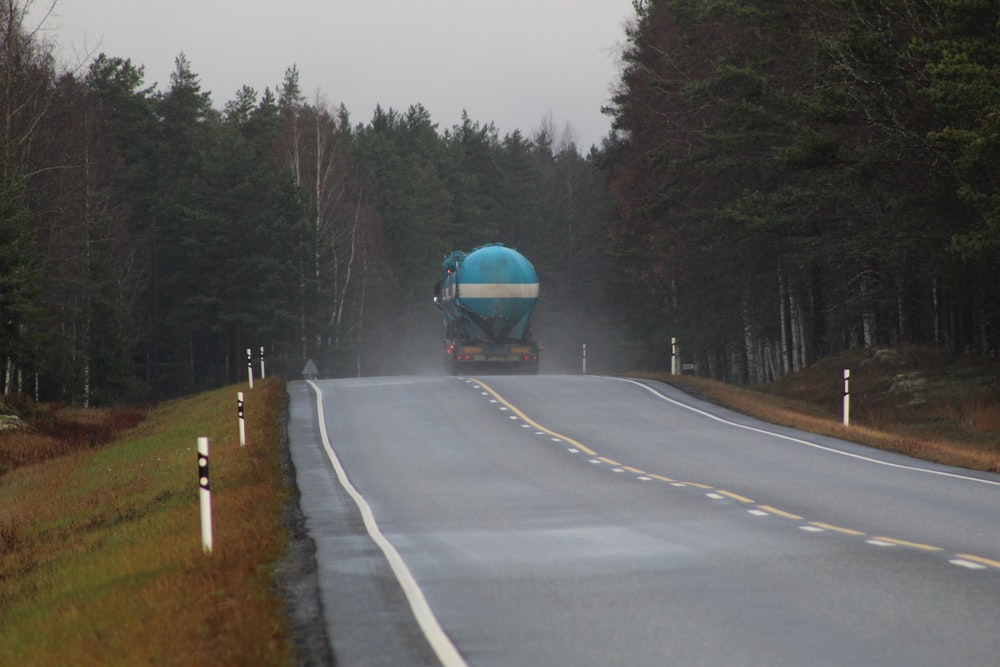 gas truck passing by an asphalt road