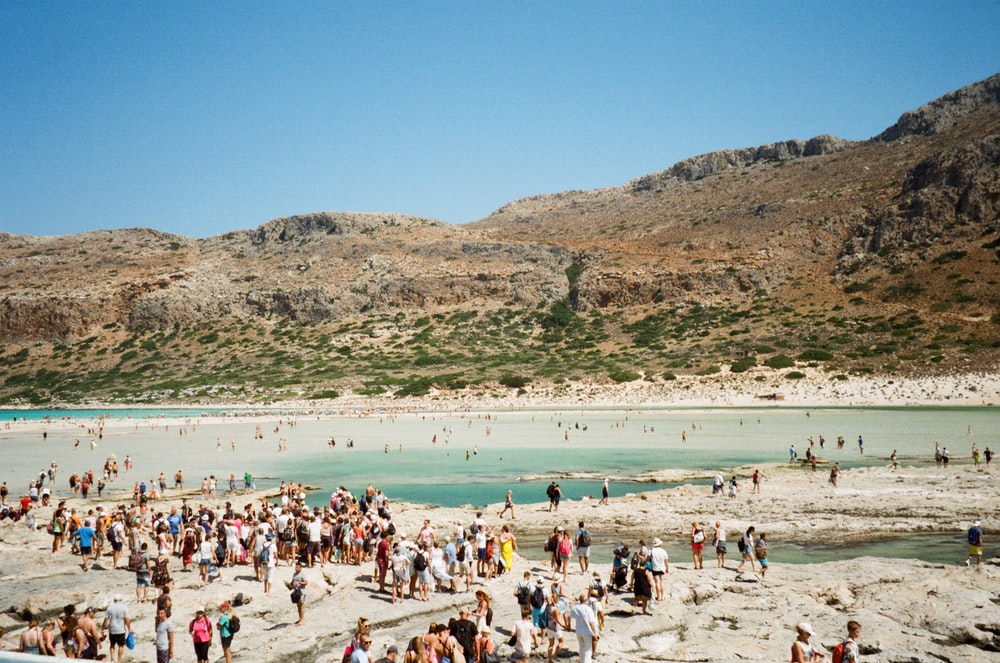 crowd of people standing and lying on beach during daytime