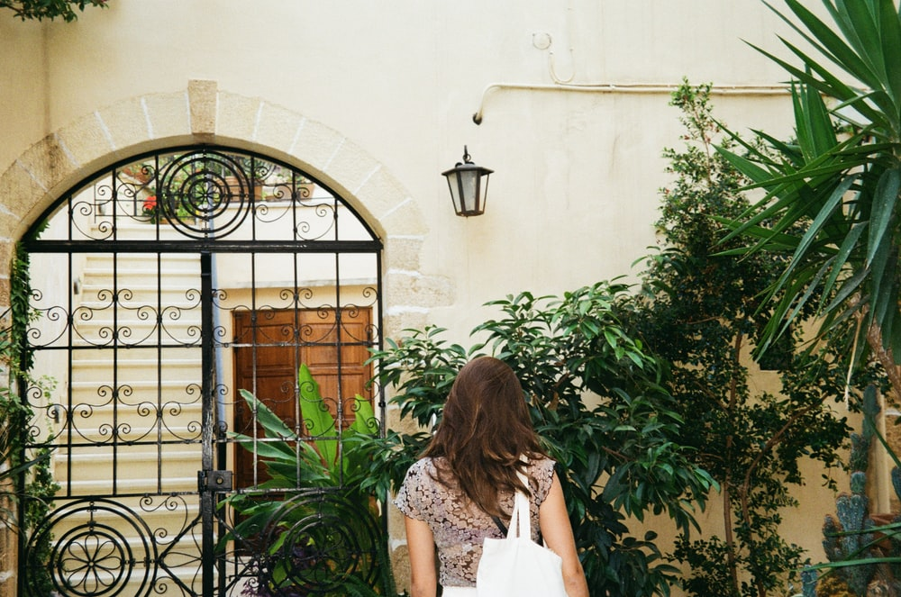 woman in white floral dress standing beside black metal gate during daytime