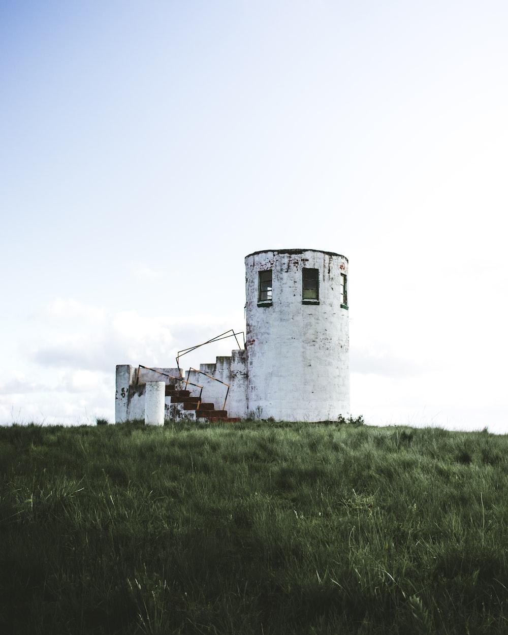 white concrete lighthouse under a calm blue sky