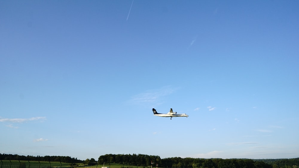 white commercial plane flying over trees during daytime