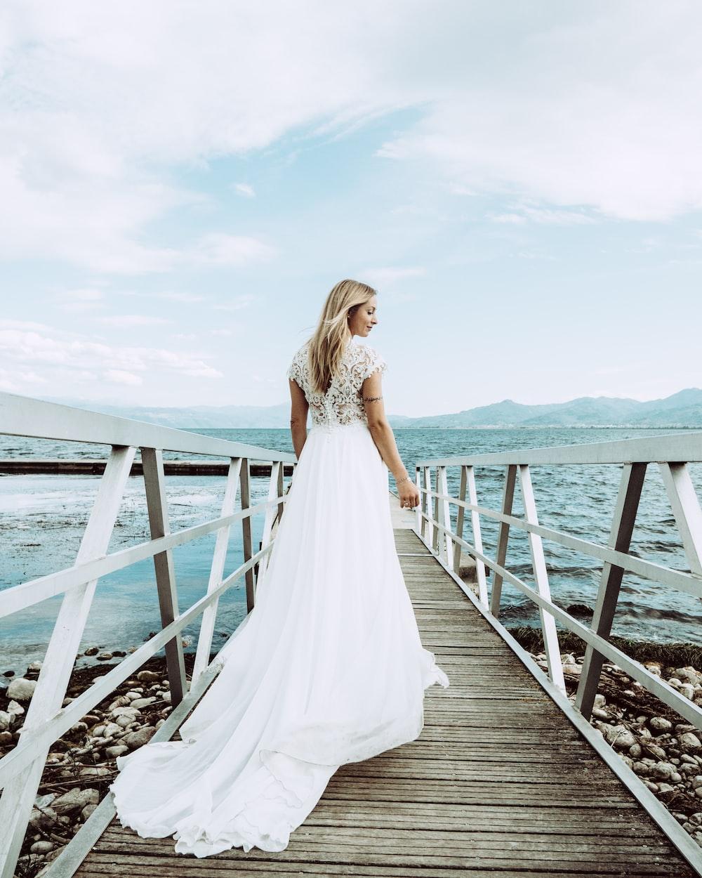 woman in white dress standing on dock bridge near seashore