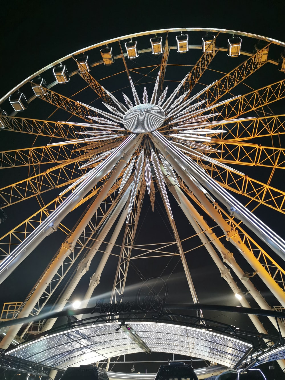low-angle photo of yellow and grey ferris wheel during night time