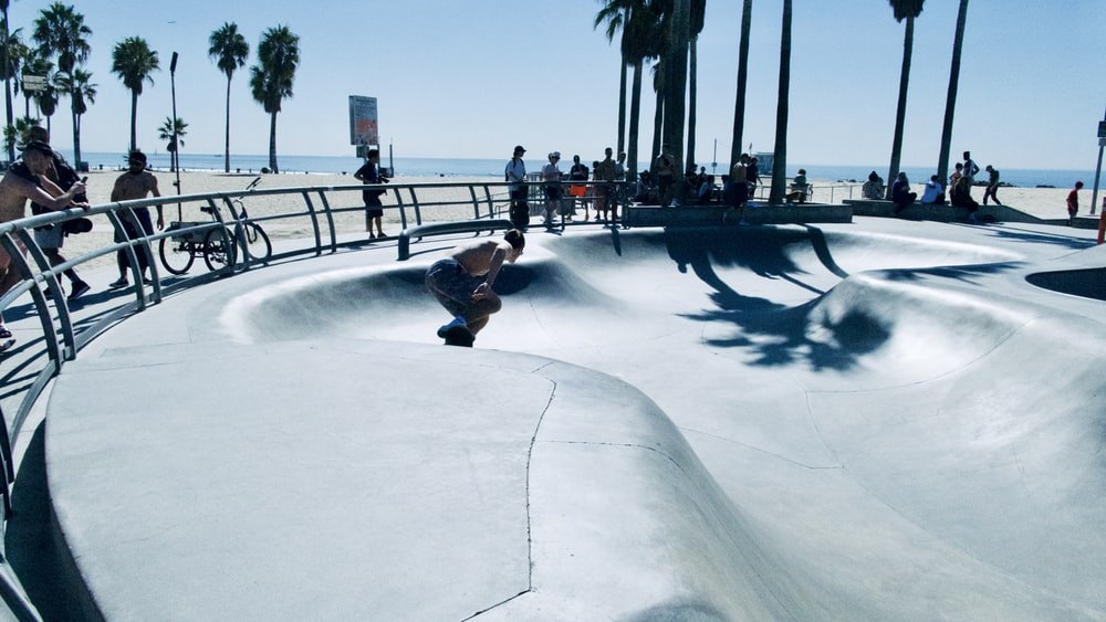 topless man skateboarding on ramp surrounded with people watching under blue and white sky during daytime