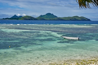 white wooden boat on sea near mountain fiji teams background
