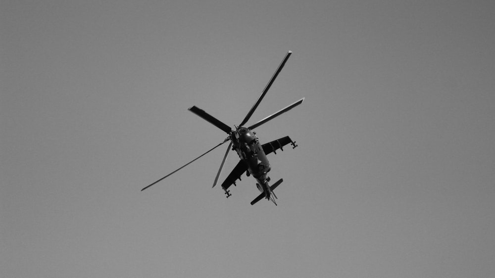 grayscale photography of flying helicopter