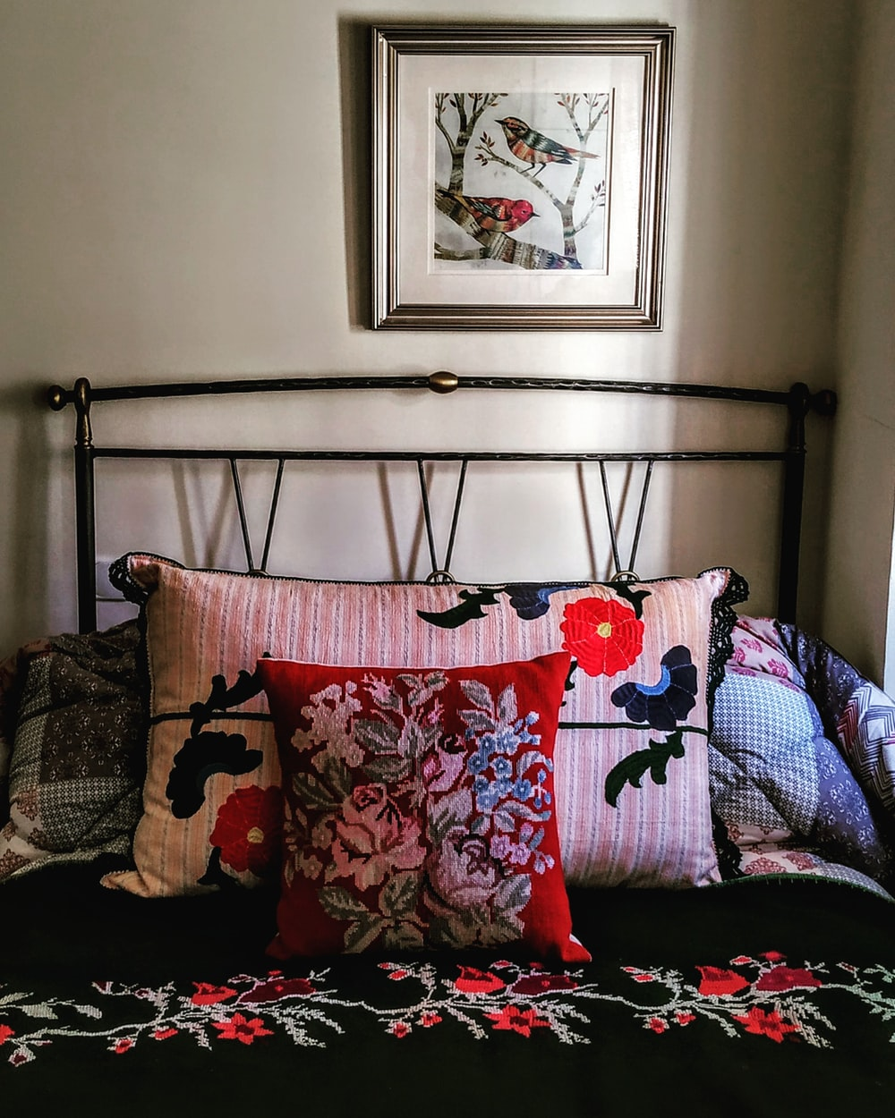 multicolored floral pillows on bed