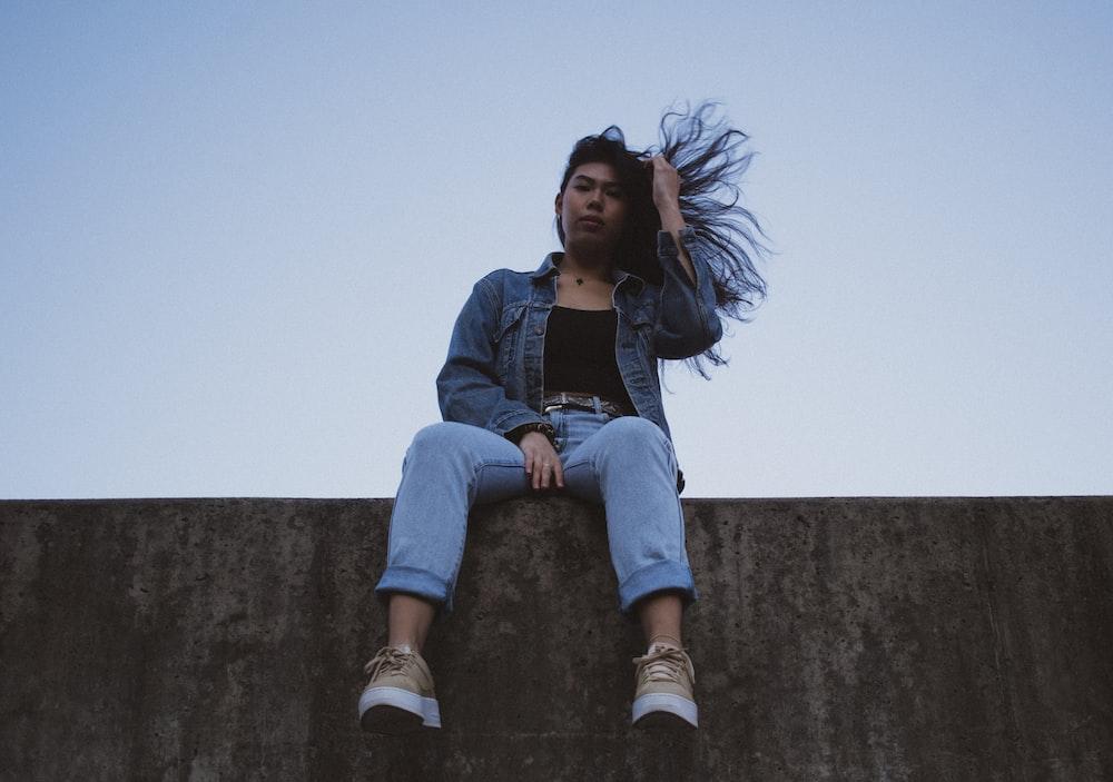 woman wearing blue denim jacket sitting while touching her hair