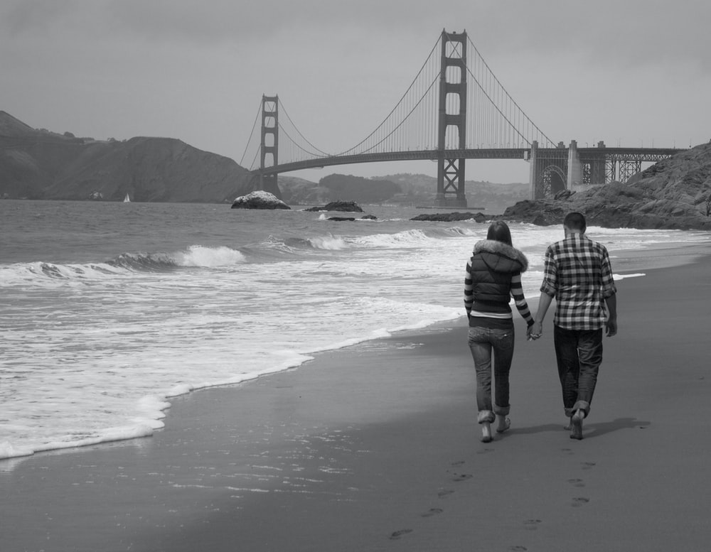 grayscale photography of man and woman walking near seashore viewing Golden Gate bridge