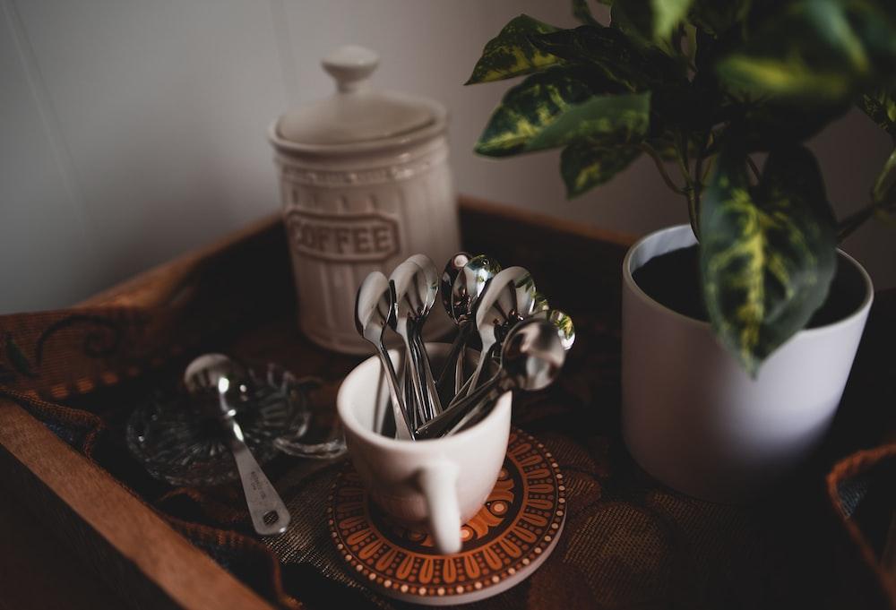 silverware in white ceramic mug beside coffee jar