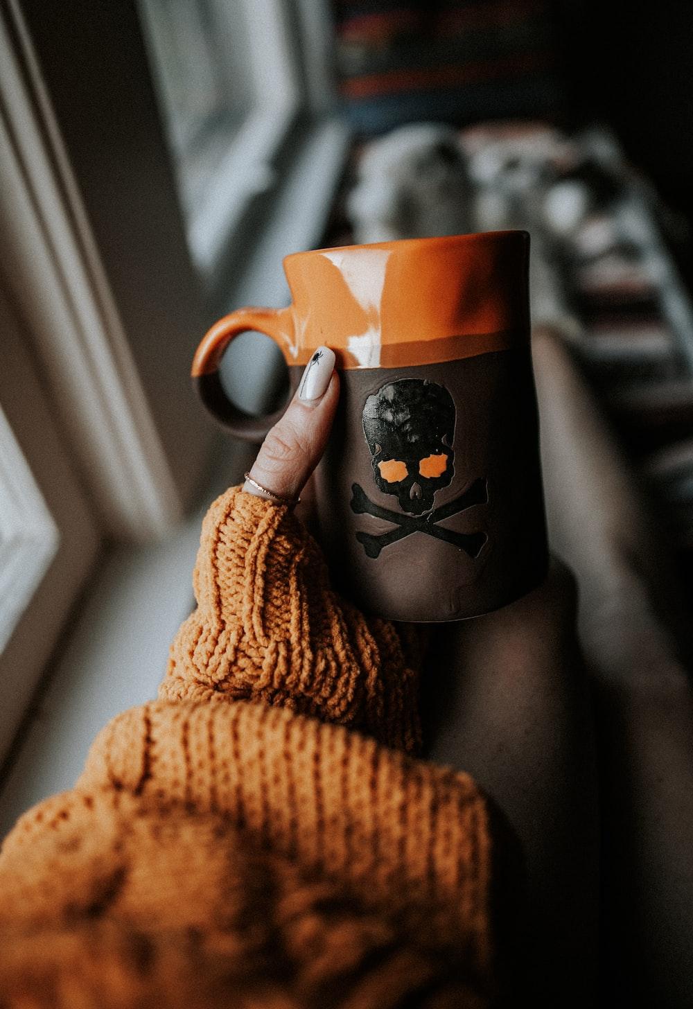 person holding orange and gray skull print ceramic mug