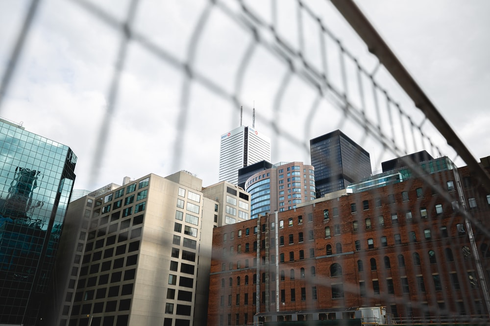 cityscape over steel fence during daytime