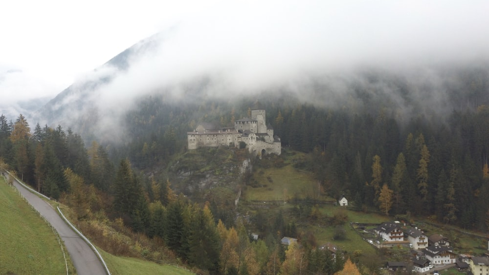 aerial photography of white castle on green field viewing mountain covered with fogs