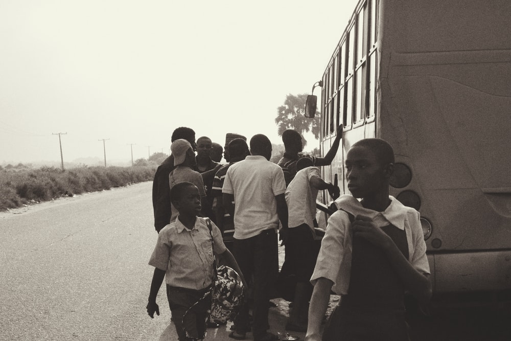 grayscale photography of people standing near bus