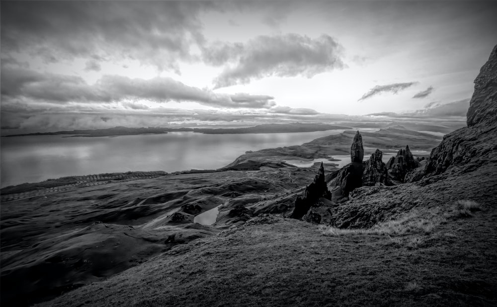 grayscale photography of terrain near body of water