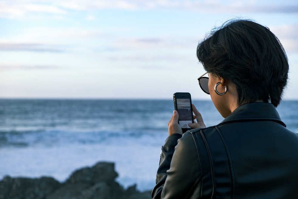 woman standing while using phone during daytime