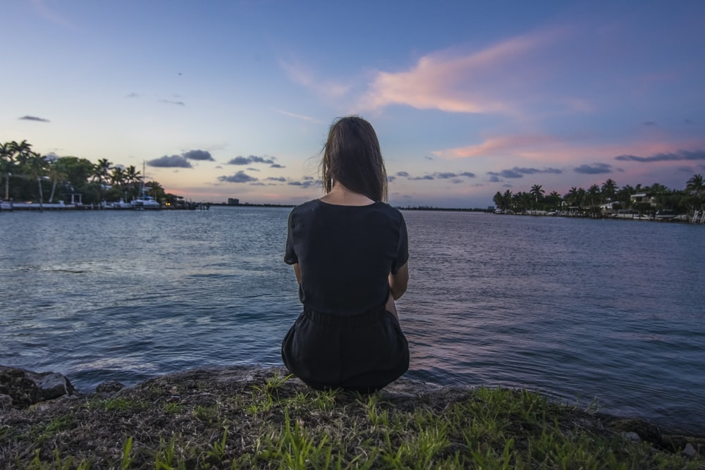 woman sitting on grass overlooking body of water