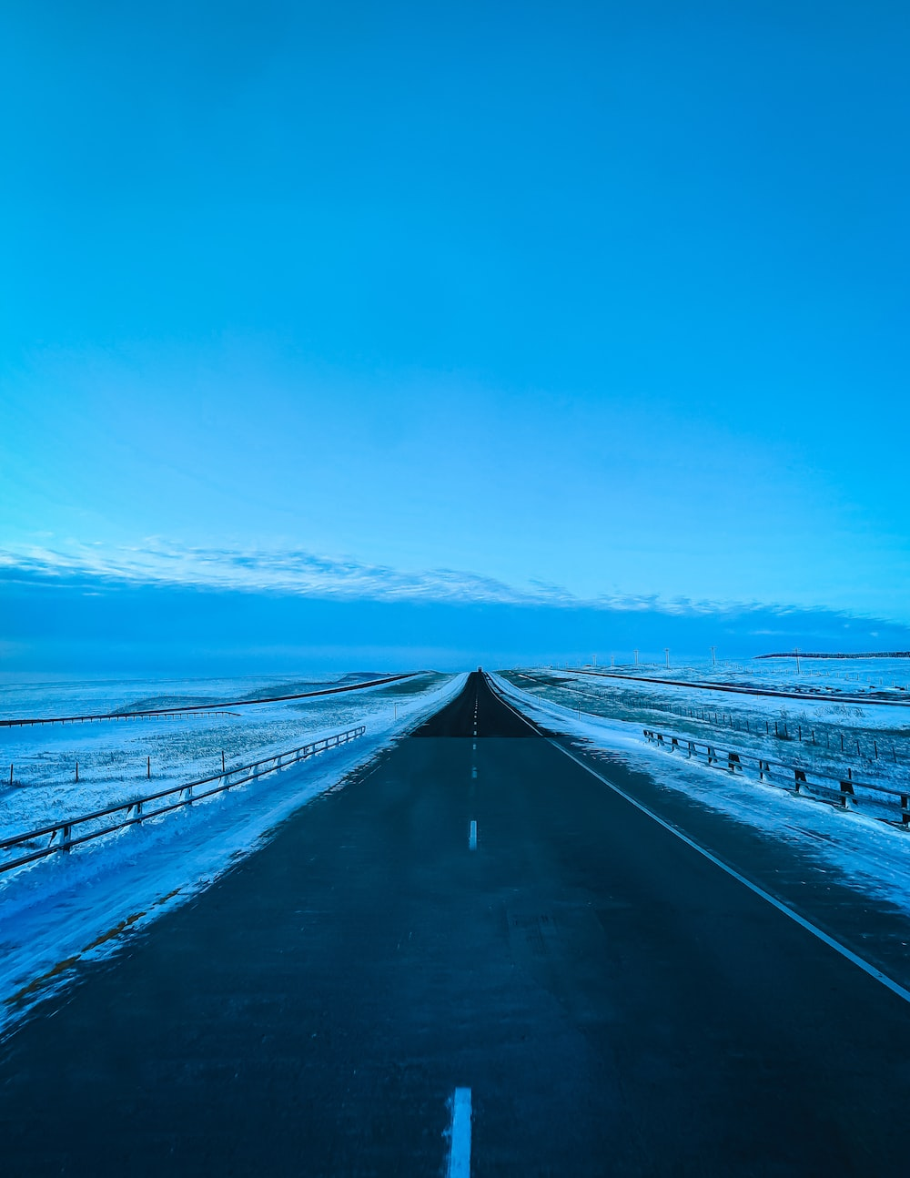 asphalt roadway beside snow field