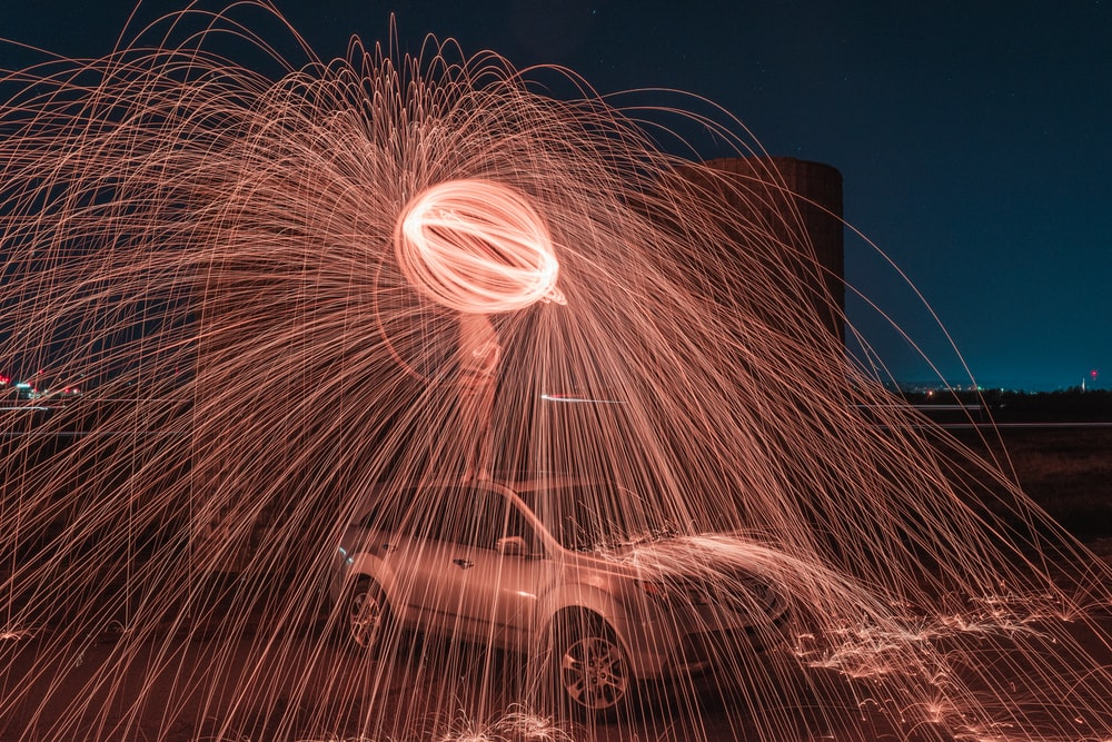 steel wool photography of person standing on vehicle at night