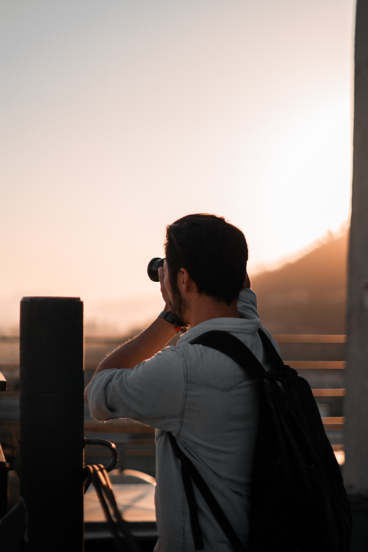 man in black backpack using DSLR camera