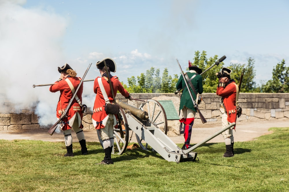 four soldiers firing canon during daytime