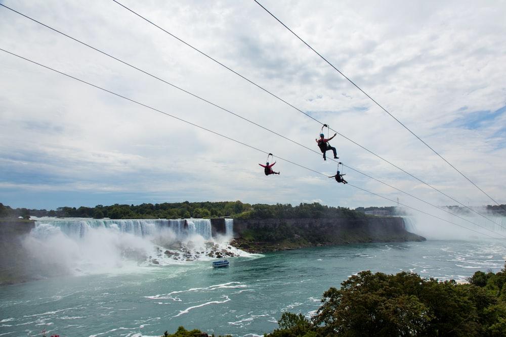three person riding on zipline