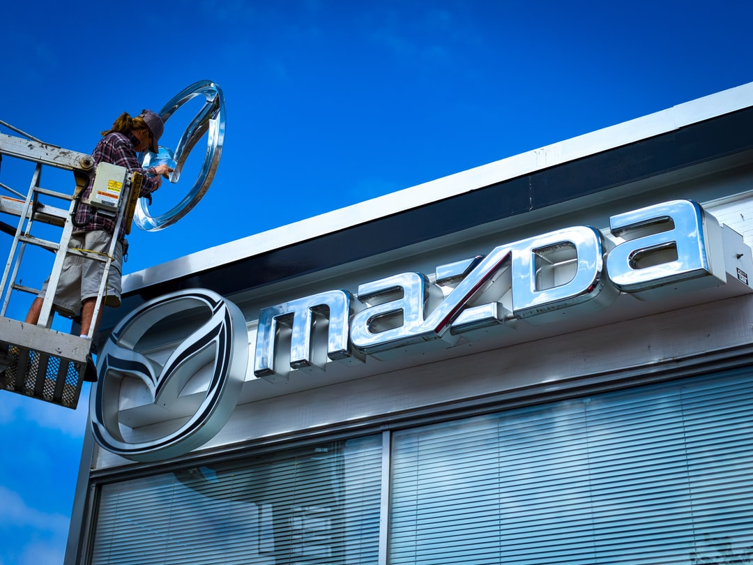 A worker replaces an old Mazda logo Marquee with the updated version.