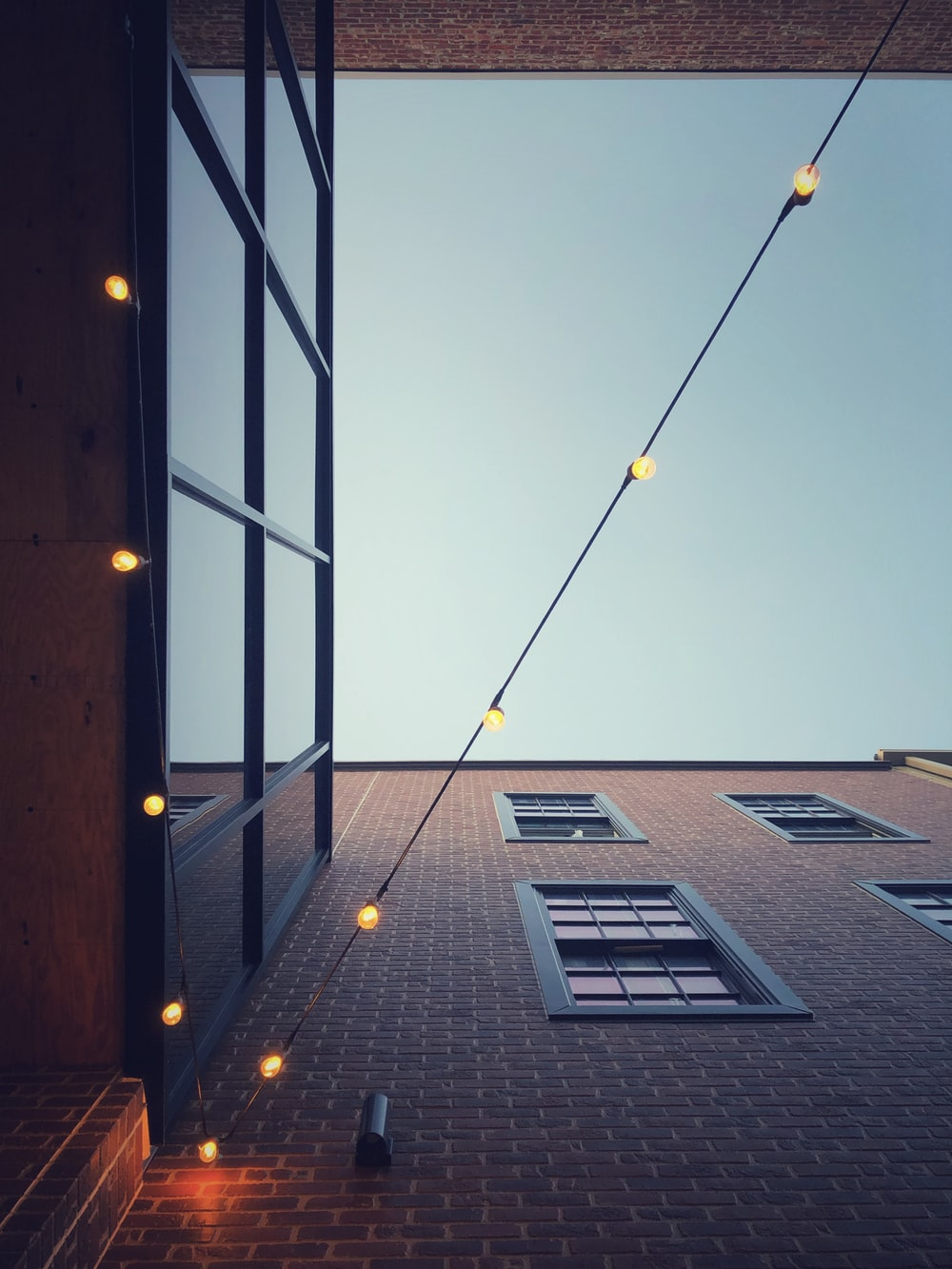 low-angle photography of turned on yellow string lights hanging on buildings