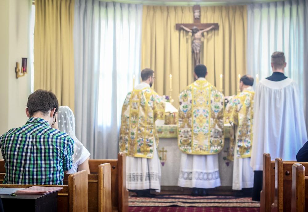 four men wearing robes standing in front of Jesus Christ cross