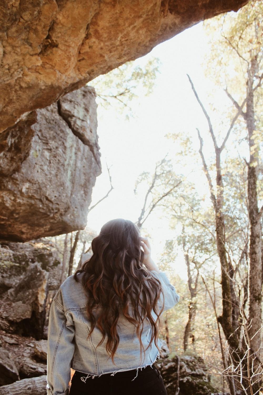 woman wearing blue denim jacket inside cave
